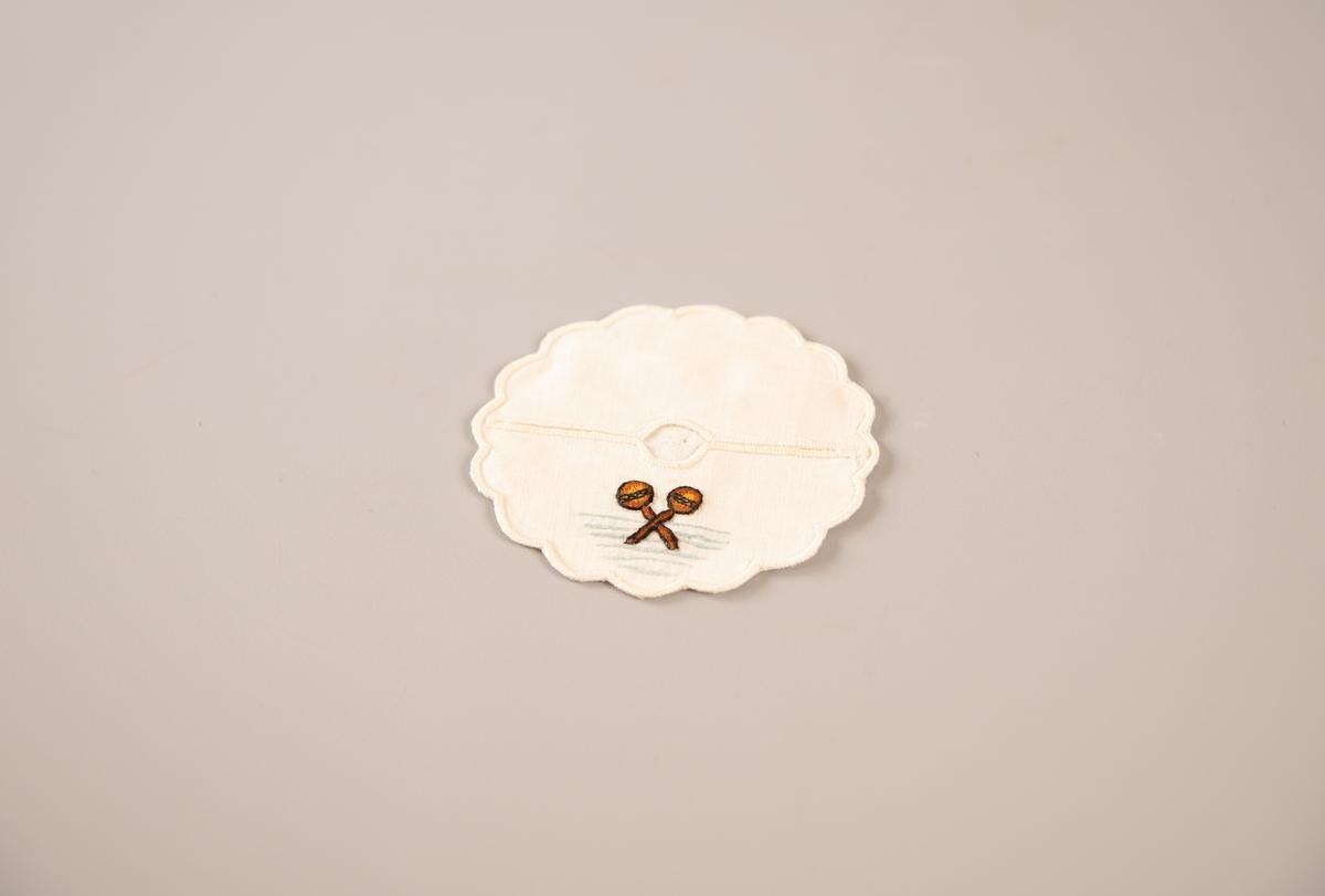 Rund bunn. På den runde bunnen er det sydd på to halvsirkelstykker med knapphullsting, slik at det blir åpen spalte over midten som stetten på et glass kan puttes i. Motiv:  To cocktailstikker i kryss i brunt over lyseblå striper.