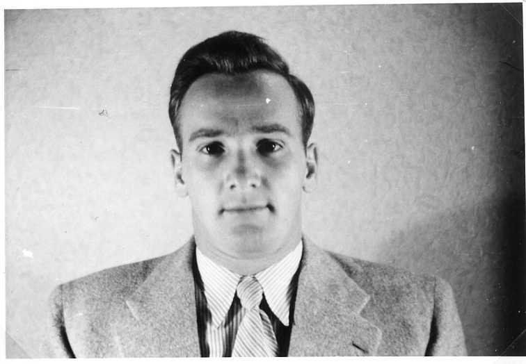 Porträtt av en ung man i kavaj och slips.
