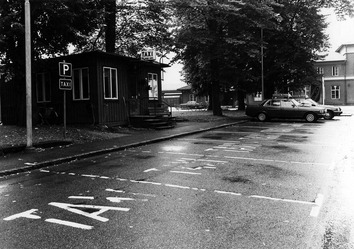 """Bilden är tagen utanför Taxistationen på Bankgatan, i Åmanska parken. Framför byggnaden ses flera parkeringsplatser med """"Taxi"""" skrivet på gatan. Taxistationen flyttade i månadsskiftet augusti-september 1982 från den gamla stationen vid Bankgatan till nya lokaler i kv. Dryckeshornet."""