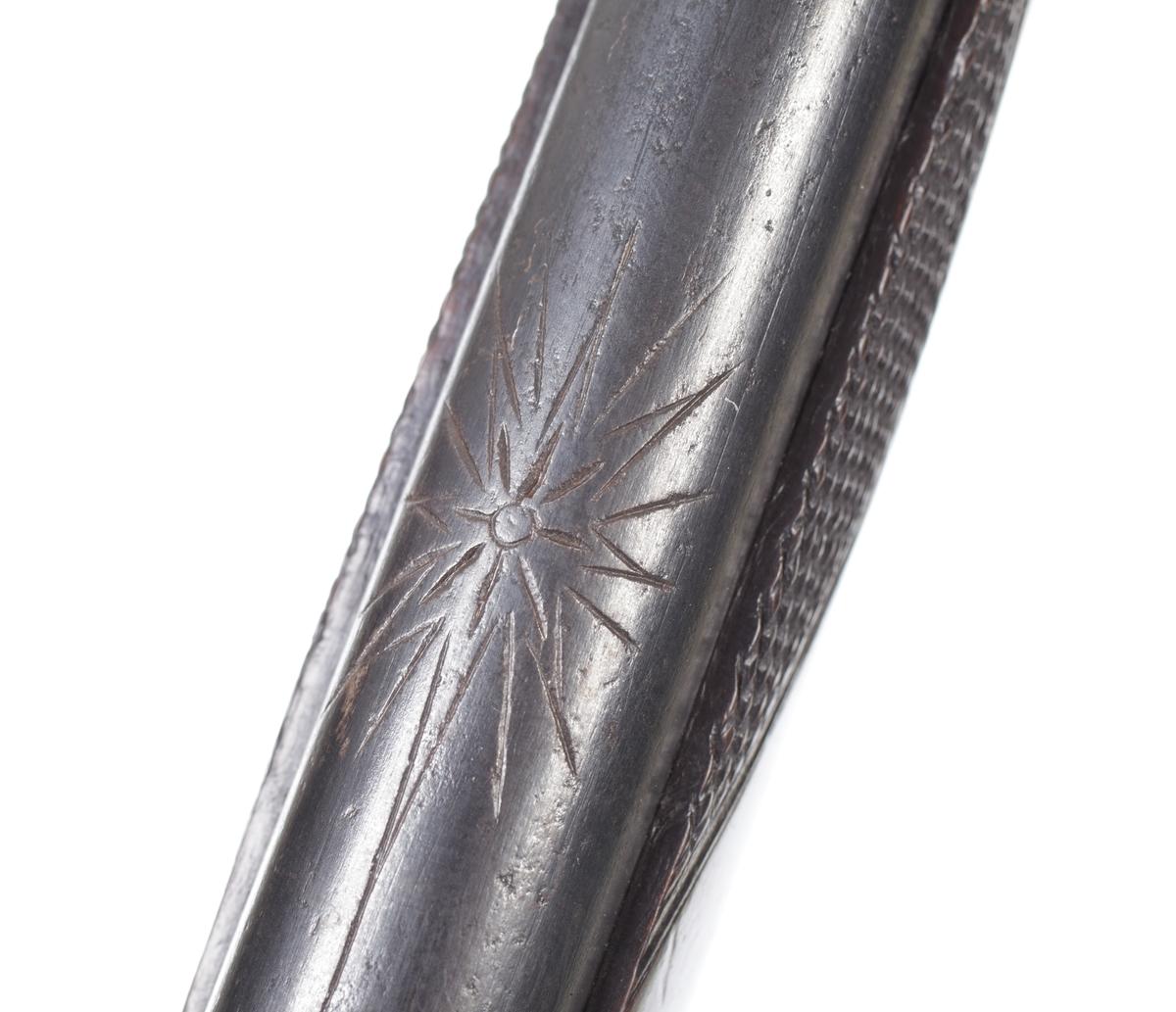 Jaktgevär försett med flintlås där framstocken går till en tredjedel av pipans längd. Under pipan finns tre rörkor vari laddstocken är inskjuten. Både framstocken och kolvhalsen har nätskärningar i rombska mönster. Kolvens bakplåt går upp över kolvryggen och avslutas med en rundad spets. Pipan är rund med en stjärnformig dekoration framför kammarstycket. Sikte saknas men vid mynningen sitter ett litet korn i mässing. Istället för sidobleck är låsskruvarnas infästning förstärkt med mässingshylsor. Låsblecket är kullrigt och försett med graverad dekor bakom hanen. Hanen påminner till formen om liknande hanar som finns på engelska armégevär från 1700-talets slut. Varbygel, näsplåt m.m. är förmodligen tillverkade av försilvrad mässing. Pipan är slätborrad med en innerdiameter på 17mm. Inskrivet i huvudkatalog ...........................................