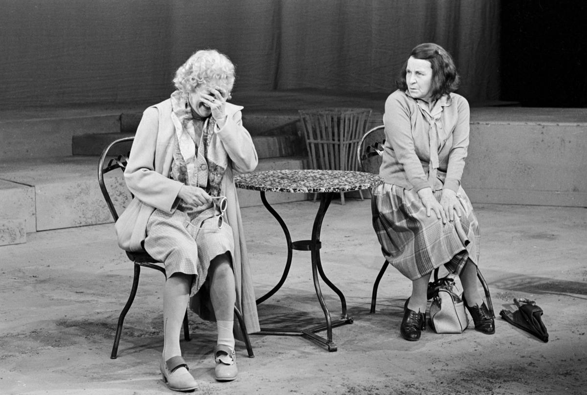 """Scene fra Nationaltheaterets oppsetning av David Storeys """"Hjem"""". Majorie og Kathleen sitter på pinnestoler ved et rundt, lite bord. Ved siden av står Harry og Jack ved en tredje stol. Forestillingen hadde premiere 27. oktober 1971. Kirsten Sørlie hadde regi og medvirkende var blant andre Ella Hval som Marjorie og Aase Bye som Katleen."""