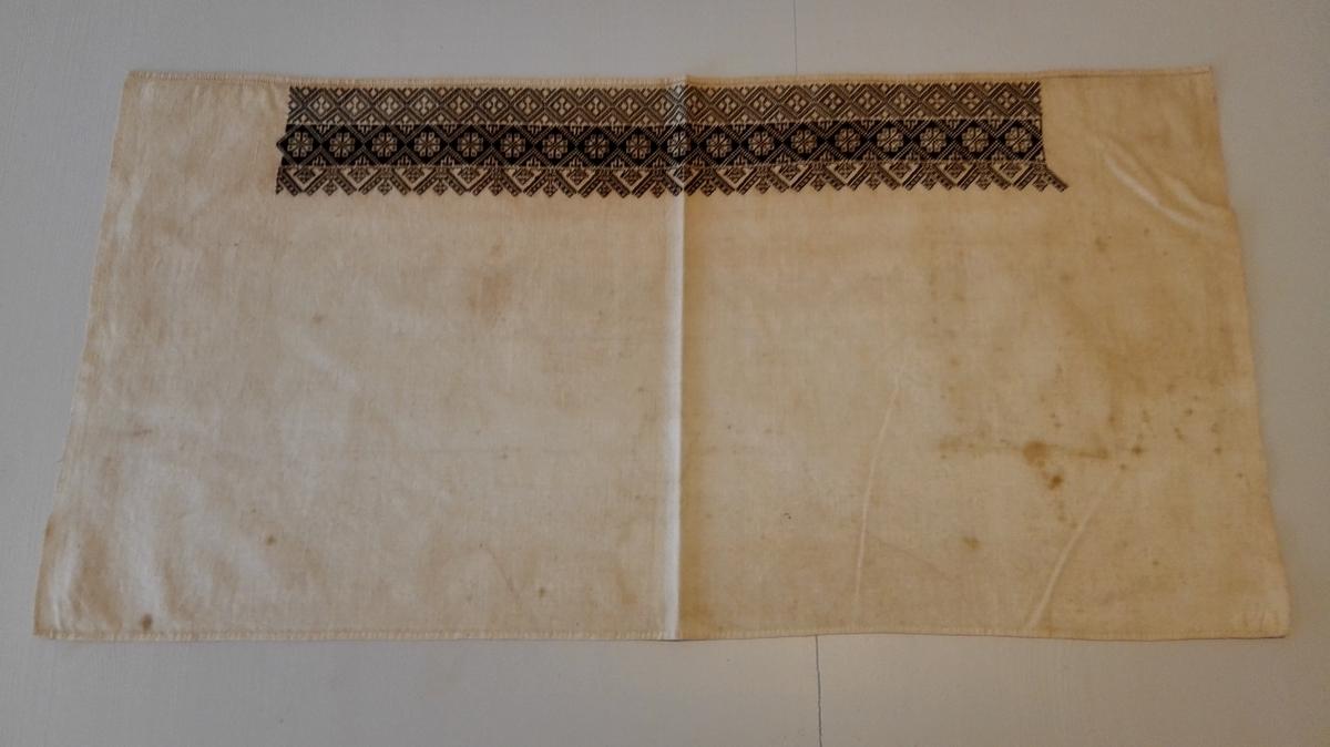 1 bleie.  En barnedaapsbleie av lin, hvorpaa utsydd en bred bord svartsaum i sort silke. Störrelse 77 x 38,5 cm.  Kjöpt av Sergeant Anders Koldingsnes, Ortnevik.