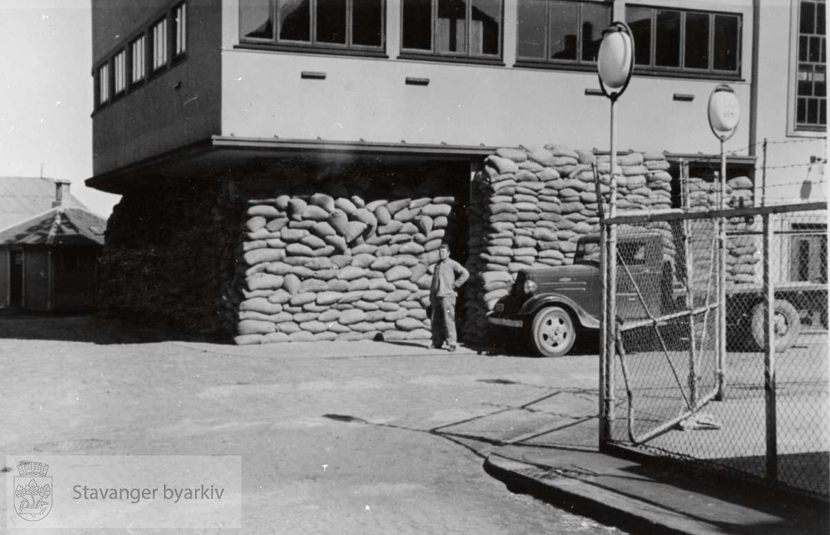 Mann og lastebil foran bygningen.