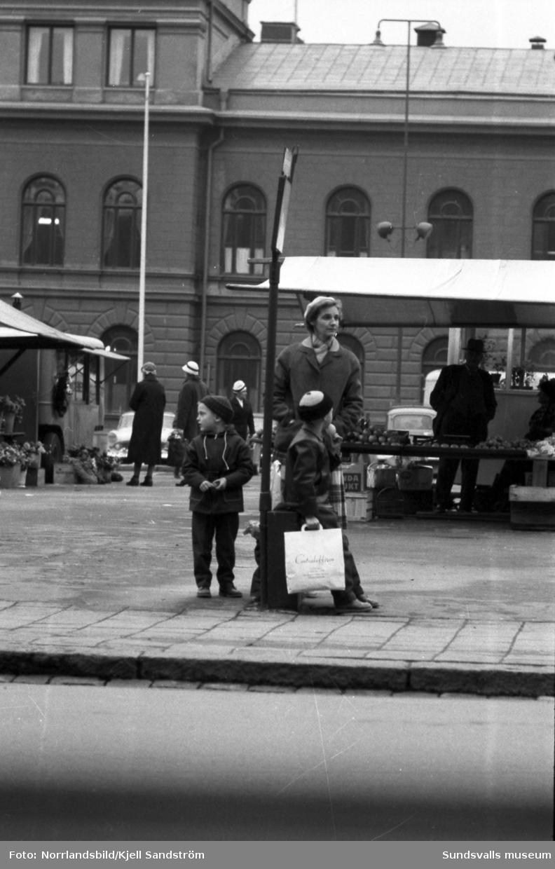 En kvinna och hennes söner väntar på bussen vid hållplatsen på Storgatan invid Stora torget. En av pojkarna håller en kasse från Centralaffären.