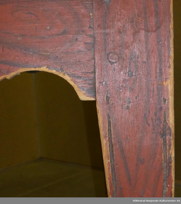 Bord med oval ubehandlet bordplate. Føtter og sarg er malt med ådringsdekor. På nedre del av føtter er malingen fjernet. Skuffer mangler, har vært to stk. Profilsaget sarg. Det er Innfrest/skåret inn to dekorspor vertikalt på føtter.