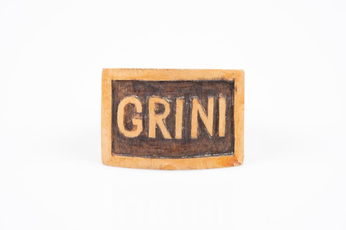 """En serviettring i tre. Framsiden er flat og firkantet med utskjæring av ordet """"Grini""""."""