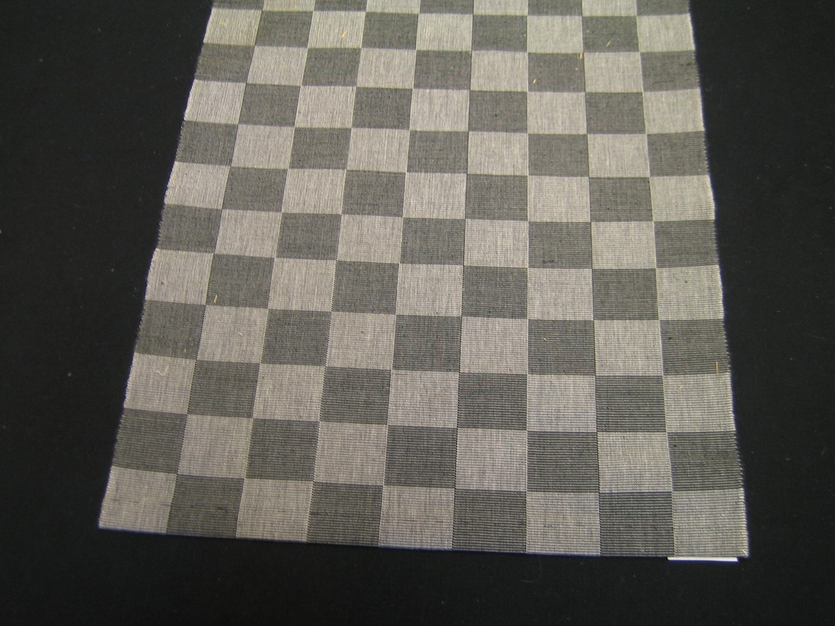 """Tre löpare SCHACK i te olika färger Svart/vit, gul/vit och röd/vit vävt i rips med nio rutor varpat i två olika färger. Rutorna är 5 cm breda. på den svartvita är en lapp påsydd med texten:""""Kvalite: Löpare Schack Bredd: 0,46 m, Material: Bomull, Längd: 1,15 m, Beställningsvara, Länshemslöjden Skaraborg Tel. 0500-10397"""". På den gulvita är en lapp fastsatt med texten: """"Löpare """"Schack"""", Storl: Bredd 45 cm, Kval.: Bomull, Pris: Material 46:-/m, SKARABORGS LÄNS HEMSLÖJDSFÖRENING""""."""