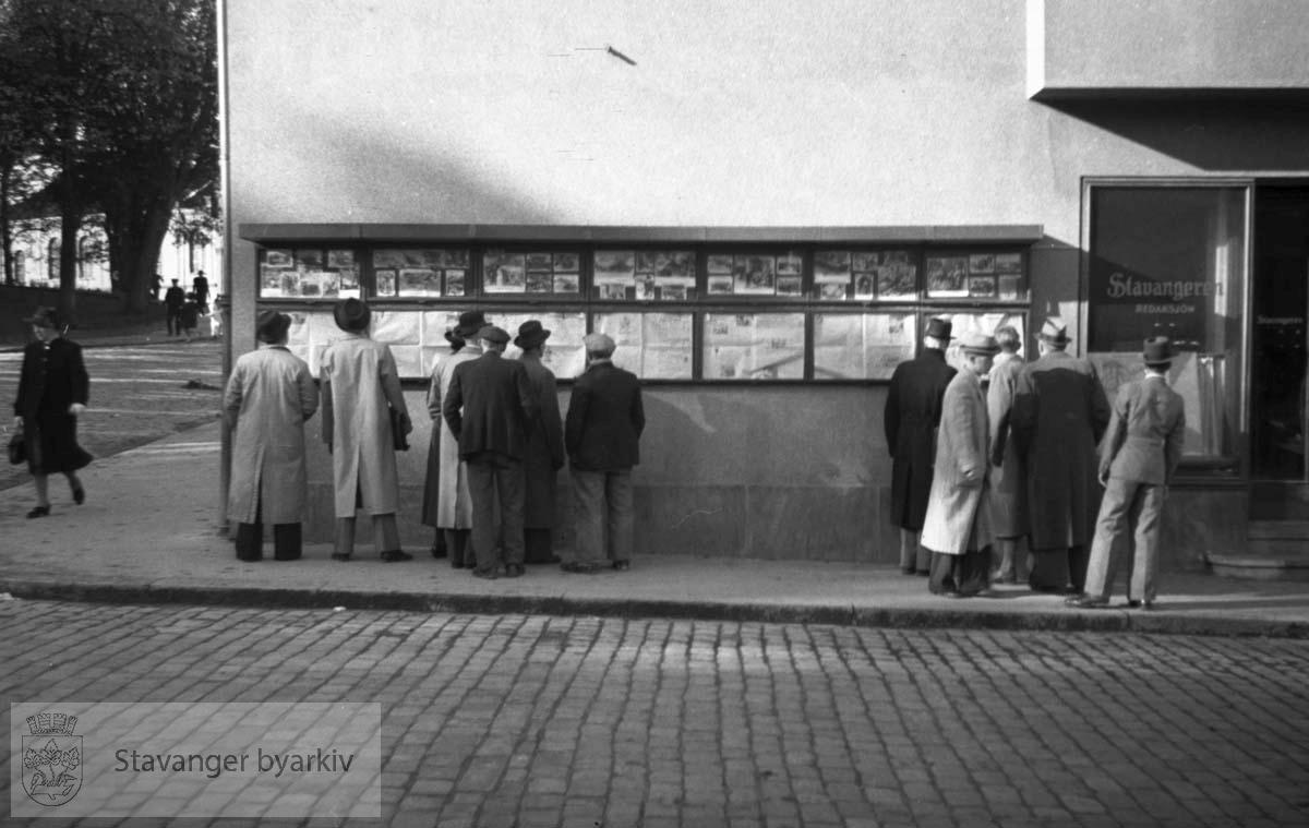 Folk leser Stavangeren utenfor avisens lokaler i Handelens Hus på hjørnet av Klubbgaten