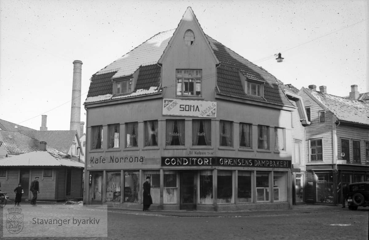 Reklameskilt for vårsalg hos Soma Skotøy lenger oppe på bygningen. Fabrikkpipe i bakgrunnen.