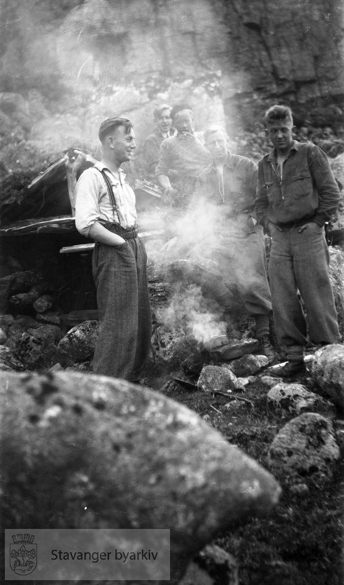Fem menn ved bål i fjellet