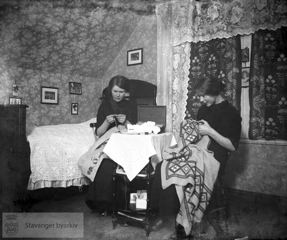 To unge kvinner sitter og syr på loftsrom med blondegardiner. (* Flere av fotografiene mellom 2000 og 2100 later til å være fra tidlig 1900-tall. Registrator stiller seg derfor tvilende til at disse er tatt av Gard Paulsen. Mulig tidlige bilder av Hans Henriksen har blandet seg inn blant Paulsen-bildene?)