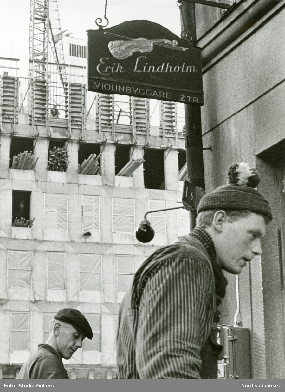 """Stockholm. Två byggnadsarbetare utanför ett hus med skylten """"Erik Lindholm violinbyggare 2 tr"""". I bakgrunden uppförs ett nytt hus."""