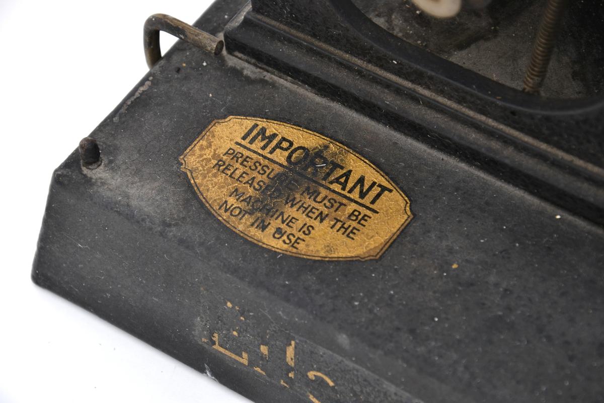 Liten sverteduplikator produsert av Ellams Duplicator Company, modell B.19, med tilhørende deksel med trehank.