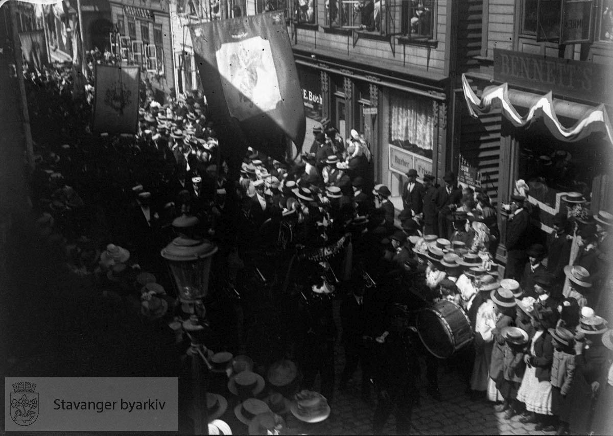 Opptoget går gjennom Kirkegata, forbi Carl E. Buchs optiske forretning i nr. 3. Dette var den åttende store sangerfesten som ble avviklet i byen. Landssangerstevne