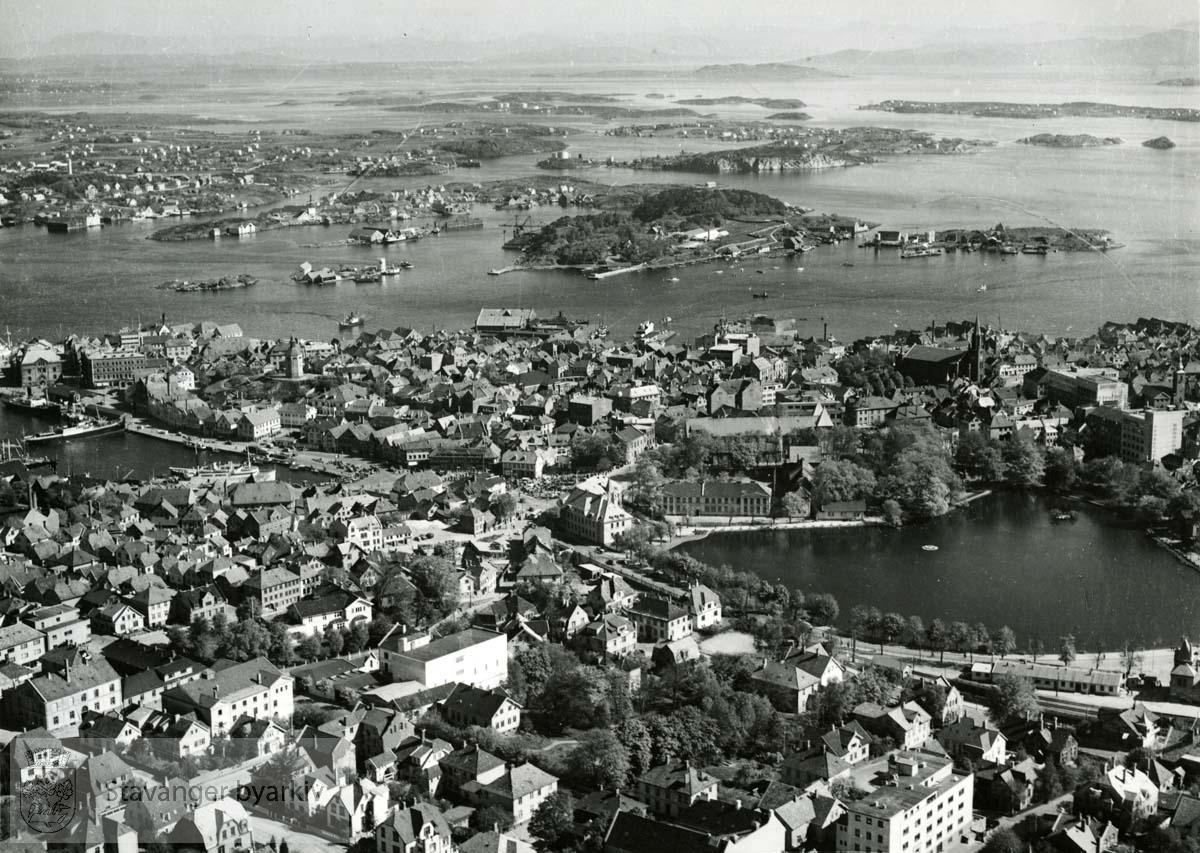 Fra venstre: Vågen, Breiavatnet og byøyene i bakgrunnen. Det katolske sykehuset nederst til høyre (bygget i 1940). Bildet er tatt før 1952...Denne serien med flyfoto fra K. Harstad, har kommunen kjøpt av Johan Ottesens Fotoarkiv. ..Karl Harstad, som grunnla K. Harstad kunstforlag (Oslo Prospektkortfabrikk) i 1925, var den første sivile flyfotoprodusenten i Norge. Som postkortprodusent var Harstad opptatt av nhye produkttyper. I 1929 dannet han sammen med andre selskapet FotoFly og kjøpte fly i Tyskland. Selskapet skulle drive både passasjerflyging og fotograferin. I 1929 fotgraferte selskapet de fleste byene langs kysten av Norge, også i Rogaland. Postkortene med flyfotografi ble produsert med navnet Flyfoto, senere med navnet K. Harstad. En annen stor K. Harstad-postkortserie fra Rogaland skriver seg fra flyfotografering 1950-1951. Da fotograferte firmaet både byer og mindre tettsteder og bygder i fylket. Det er uvisst hvor omfattende K. Harstad sin flyfotoproduksjon var i Rogaland før firmaet ble nedlagt ved overgangen til bruk av fargefoto tidlig på 1960-tallet. Så langt man kan se av postkortsamlinger ved kulturverninstitusjonene og hos private, viser de aller fleste kortene byer og tettsteder, ikke enkelteiendommer og bedrifter.