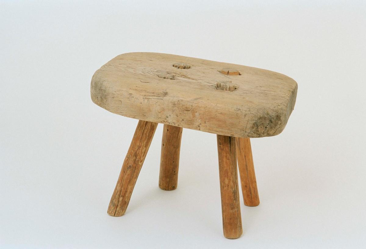"""Liten pall av omålad furu, enkel tillsågad sits med itappade ben, varav ett nytillverkat enligt huvudliggare. """"1788"""" skuret under sitsen."""