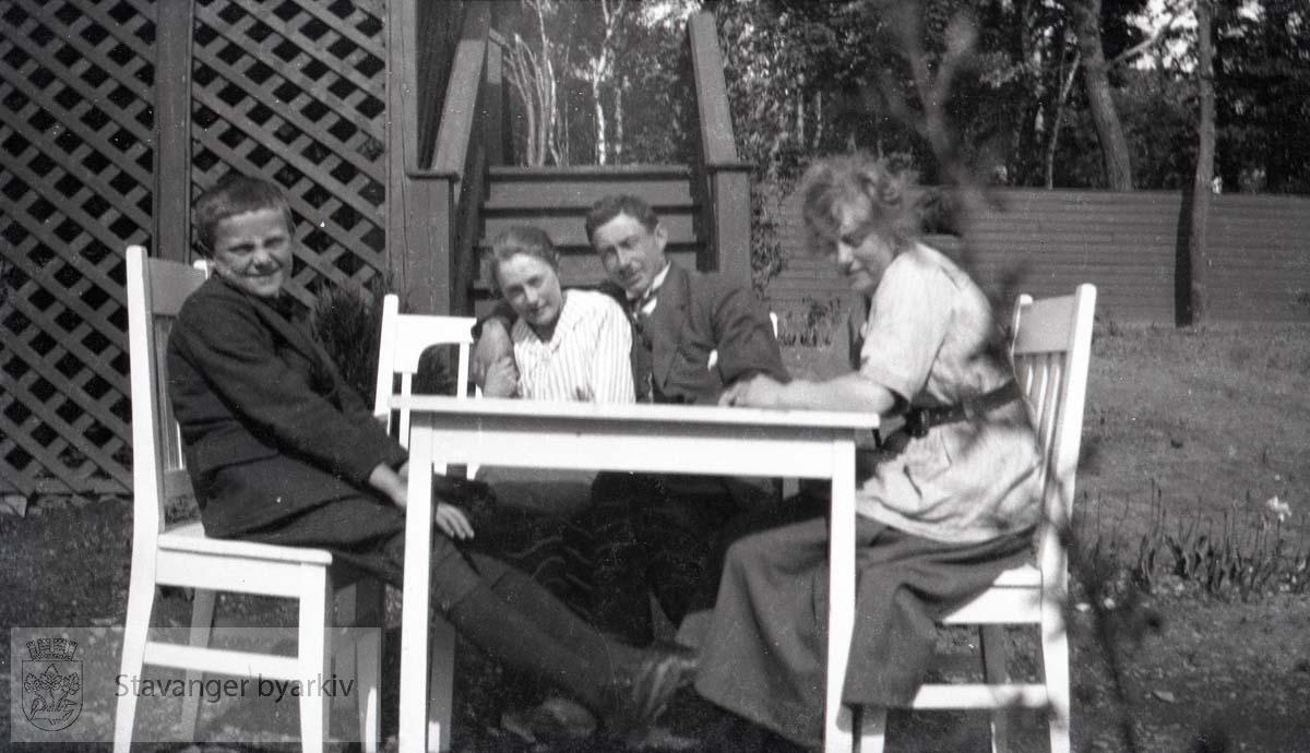 Fire personer samlet rundt bord i hagen