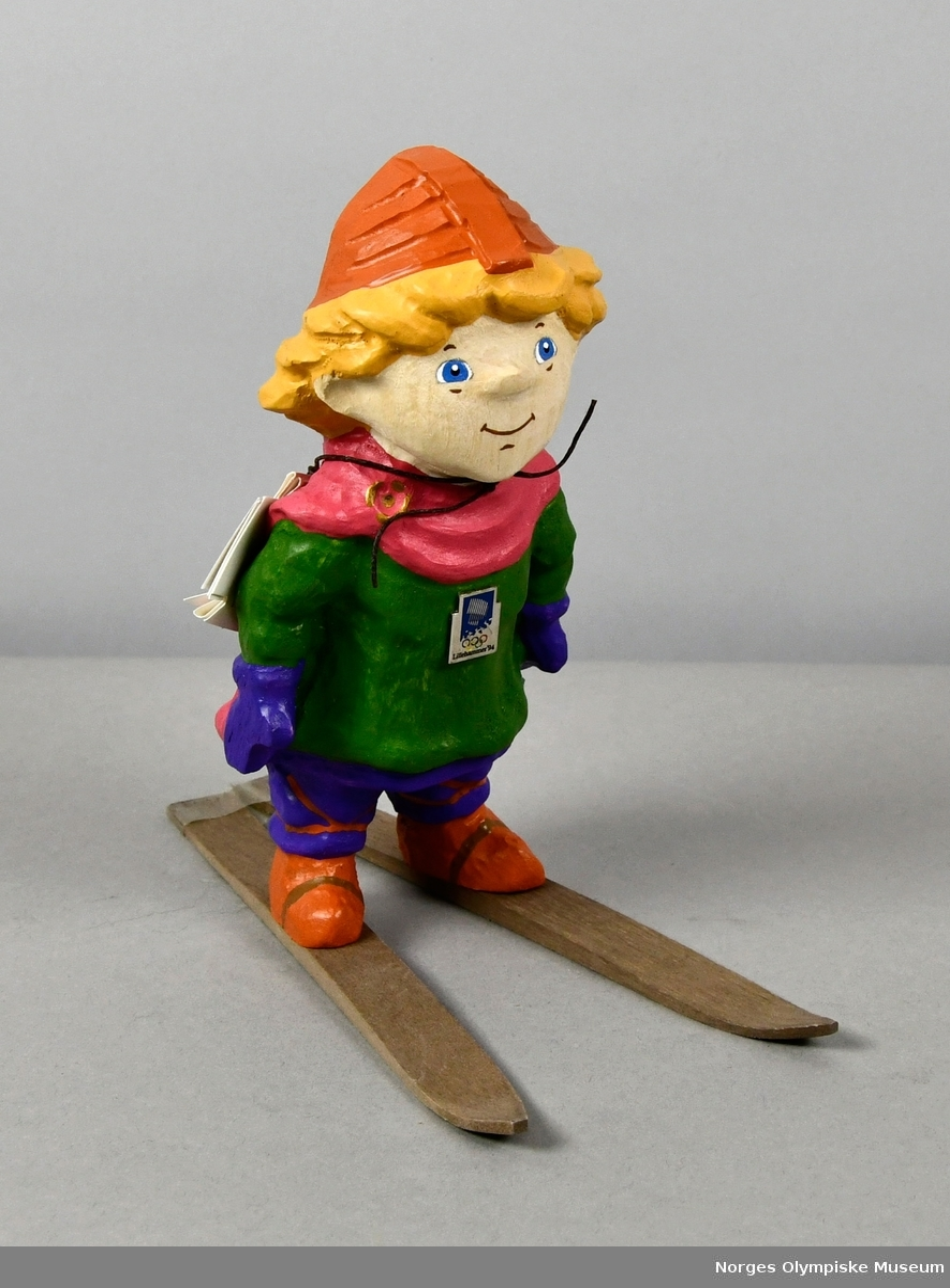 Figur av tre som forestiller maskoten Håkon som går på ski. Han har hjelm, rosa kappe, grønn genser, lilla bukser og lyse brune sko og ski.