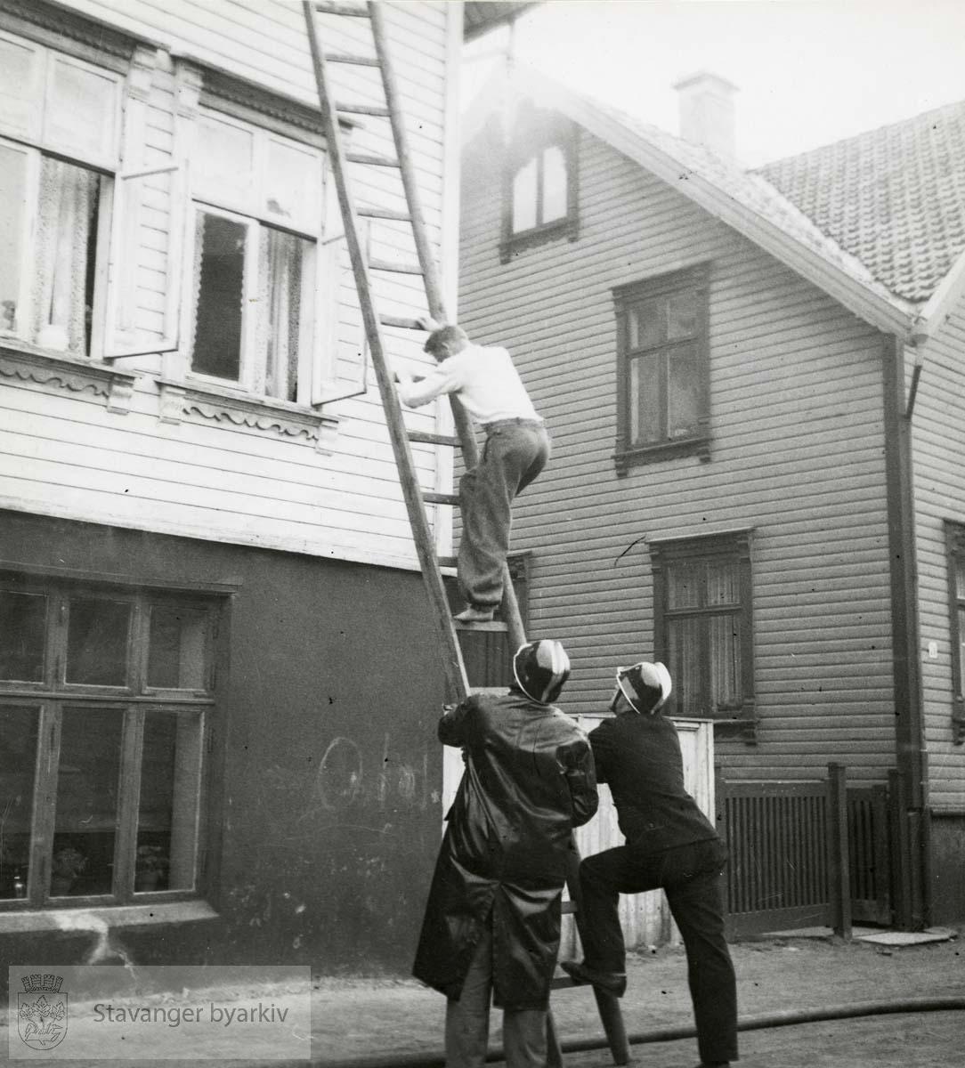 Mann hjelpes ut av brennende hus.
