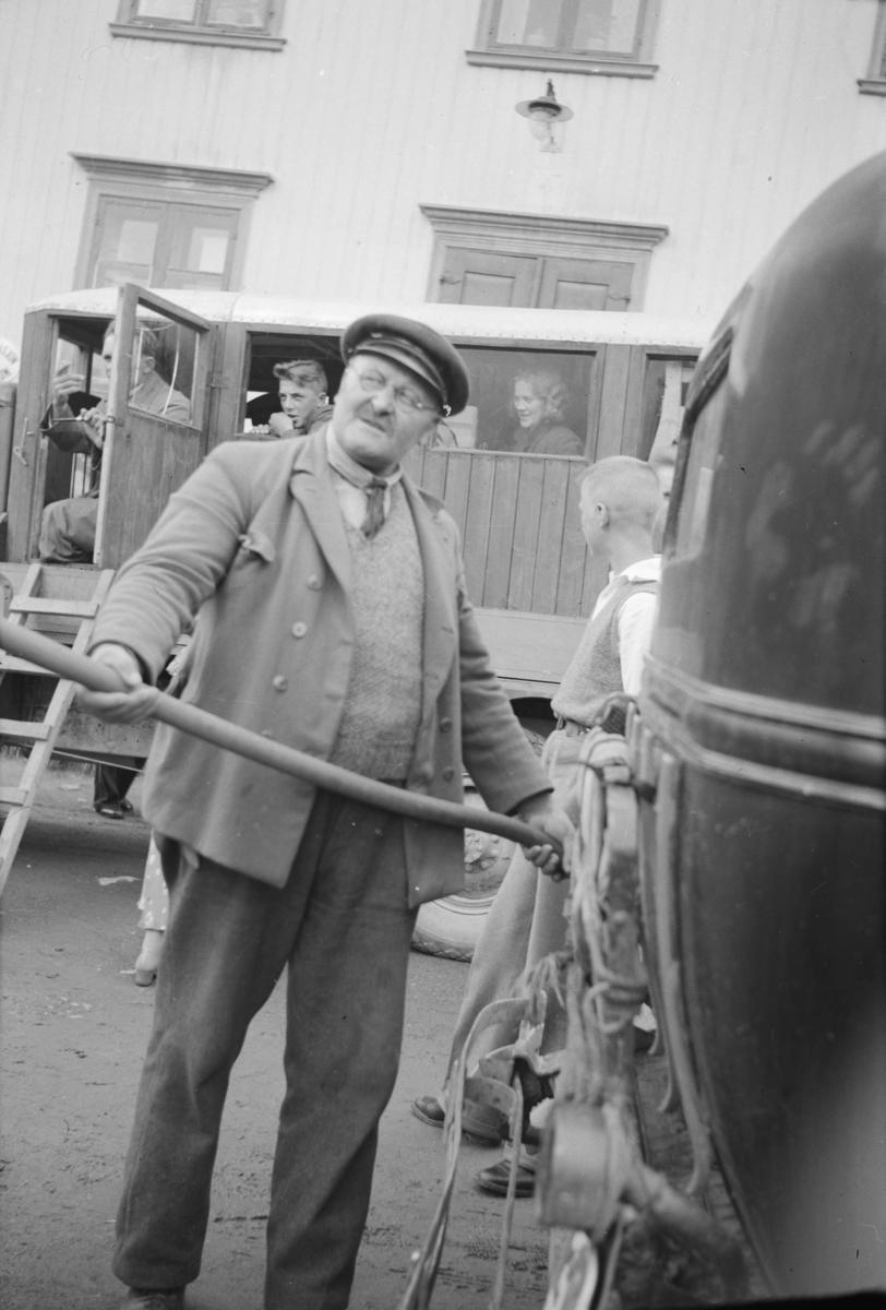 Drosjesjåfør Erik Solvang fyller bensin ved butikken på Linjordet, lastebil med busshus i bakgrunnen