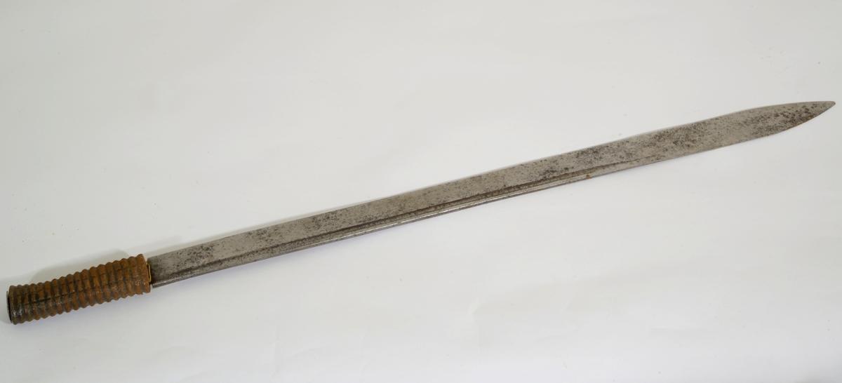 Rillet jerngrep fra en marinehuggert ca 1800-1820. Enegge,t kileformet, rett klinge med smal ryggstillt blodrand. Hylseformet kappe med oval forhøyning for nittingen. Klingen er tveegget mot den midtstilte spissen.