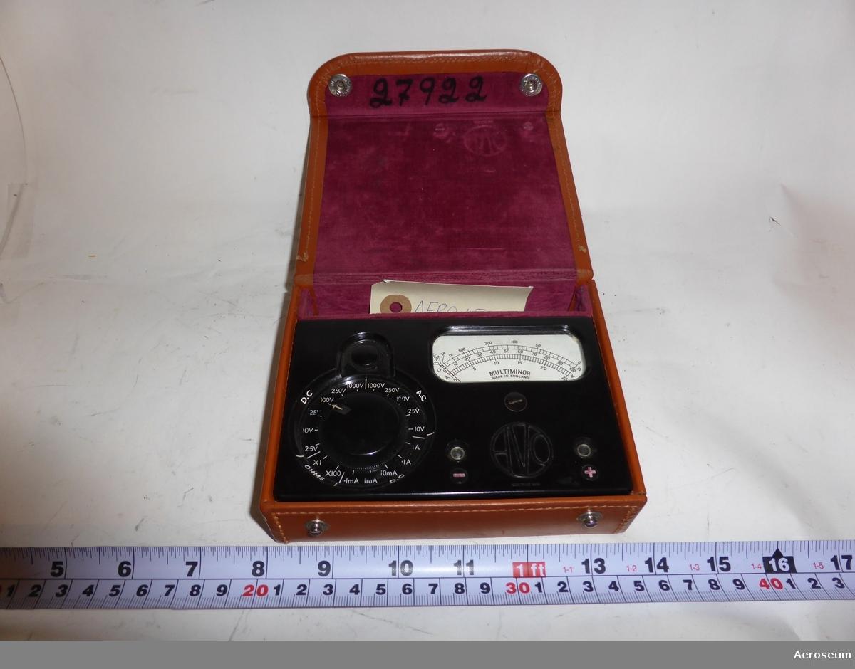 """En svart URI-meter i brun läderförpackning. På lockets insida står det: """"27922"""", detta nummer står även på själva URI-metern. På föremålets display står det """"MULTIMINOR MADE IN ENGLAND""""."""