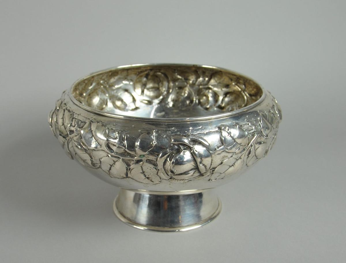 Stettebolle av sølv, med siselert dekor. Motiv på dekor av borde med blader og blomster.
