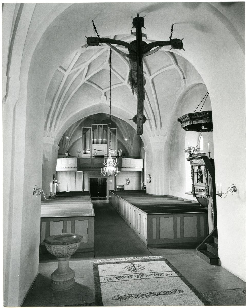 Badelunda sn, kyrkan. Interiör mot kyrkorgeln med dopfunt, bänkar m.m., 1983.