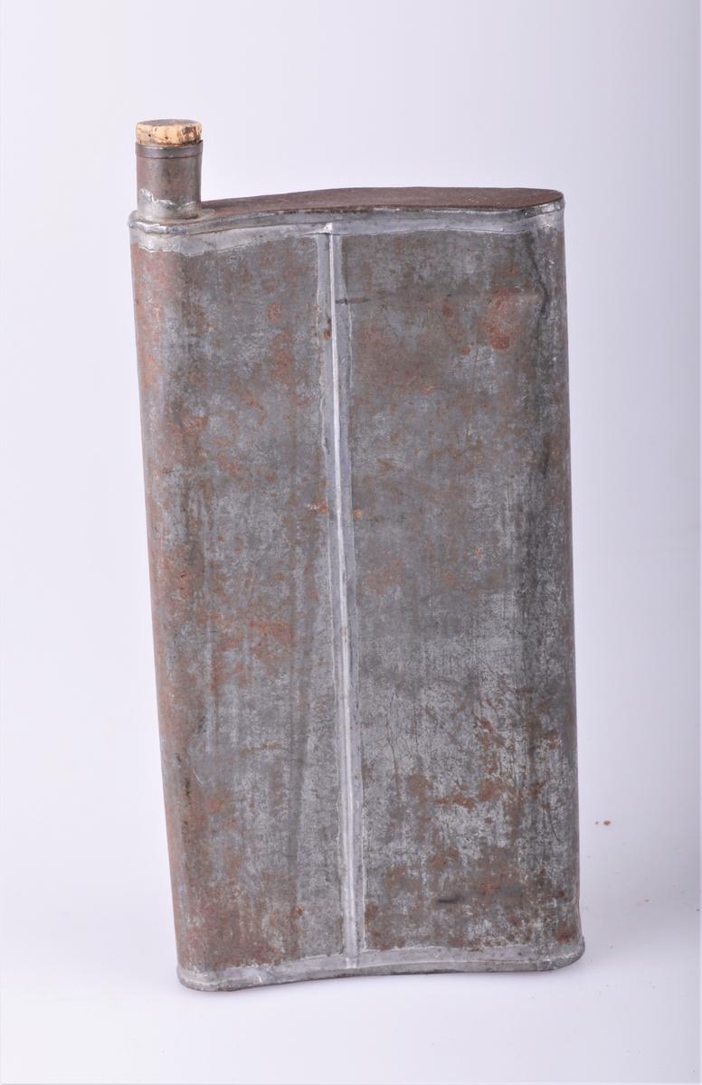 Brennevinsbelte bestående av tre deler. a) kobbertank med to bærestropper av lerret, en til å ha bak nakken og en til å spenne rundt livet. Tanken har åpning med helletut og gjenger til å skru fast en kork. b) mindre messingtank til å bære innenfor den største. Har to metallhemper slik at den kan henges opp i stropper, og åpning til en kork. c) blikkflaske med kork. Alle tre tankene er buet i formen slik at de kan bæres nær kroppen.