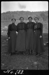 Gruppebilde av fire kvinner, fotografert stående utendørs.