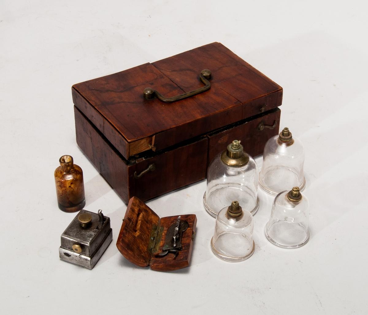 Verktyg för åderlåtning placerade i en trälåda. Verktygen är två glasskålar, en liten glas flaska, en liten trälåda och en okänd apparat i metall-troligtvis till för att skära/sticka hål i huden har en spännmekanism som sen går att utlösa .