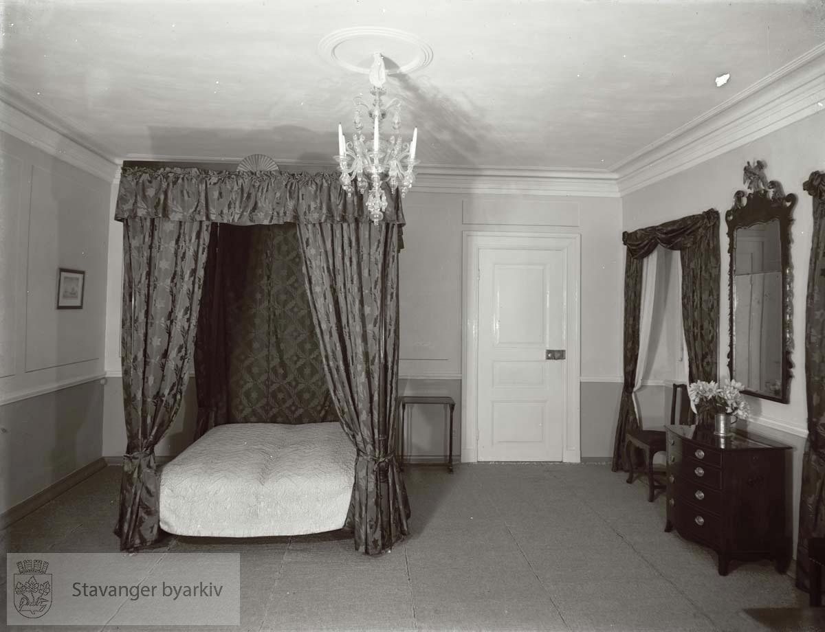 H.M. Kongens værelse med bl.a. himmelseng, speil, kommode og stol.