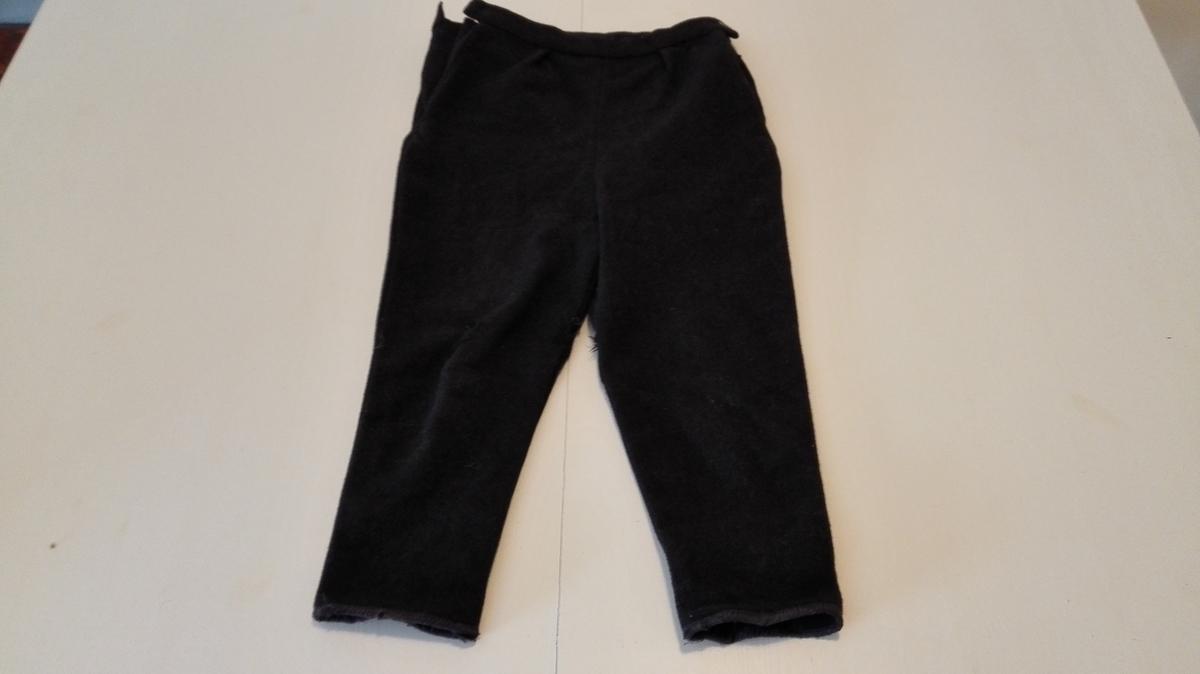 Strekkbuksefasong med smalnande buksebein kanta med anna stoff. 2 legg framme 4 innsnitt bak. Opning med knappelukking og innfelt kile i opning i båe sider.