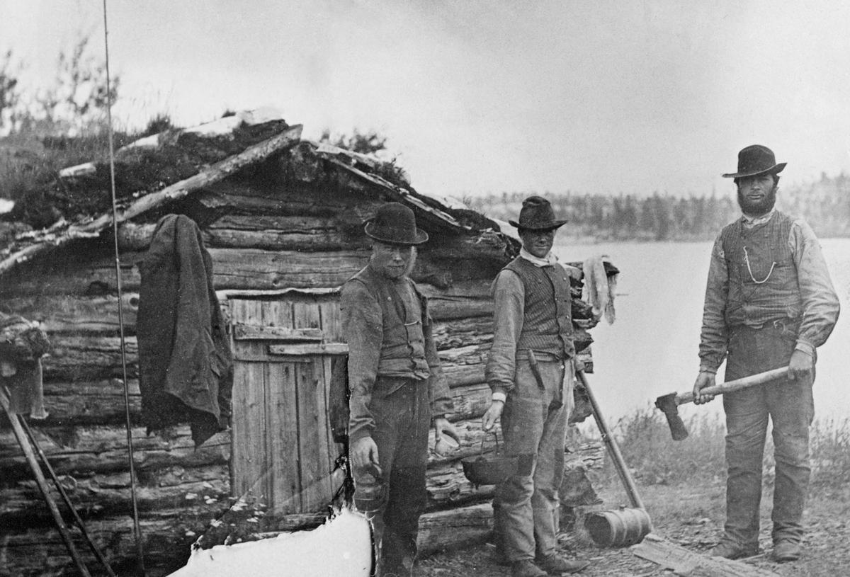 Tre menn, fotografert framfor ei bu ved øvre eller nedre Roasten i Femundsmarka, antakelig i 1880-åra. Dette er to små innsjøer som ligger i Røa-vassdraget, på grensa mellom Engerdal og Røros kommuner og dermed også mellom Hedmark og Sør-Trøndelag fylker. Vi har ikke navnene til de tre karene, men de var antakelig reisefølget til en av de engelske advokatbrødrene Richard Ford Smith og Charles Lassow Smith, som hvert år kom til Engerdal for å fiske med flue og fotografere. Dette fotografiet er tatt framfor gavlveggen og inngangsdøra til ei laftet, torvtekket ljørkoie, som karene sannsynligvis brukte som kvilested. En av dem sto med en kaffekjele i handa, en annen med ei jerngryte og den tredje med ei øks. Sistnevnte skulle antakelig hogge ved til kaffekoking og matlaging.  Ved veggen i bakgrunnen skimter vi to fluestenger. Her hadde fiskerne dessuten hengt klær til tørk.