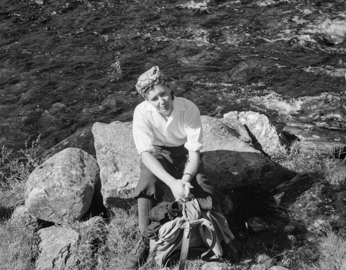 Kvinne på tur - rast ved vann eller elv