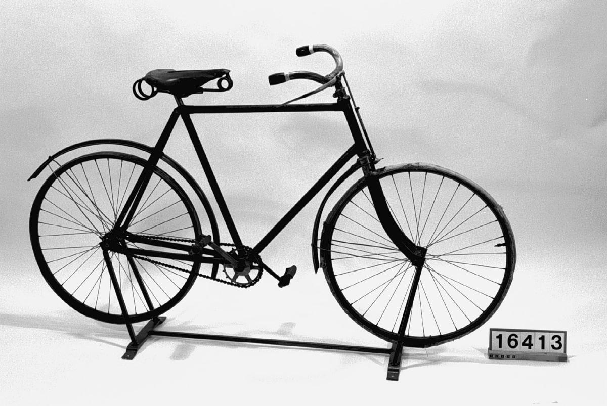 Tvåhjulig cykel med luftringar och fast kedjedrift på bakhjulet. Ram av stålrör med skärmar av plåt och fjädersadel klädd i läder. Ringklocka på styret. Svart med gröna ränder på skärm. Höger pedalvev och kedjekrans utbytta liksom skärmar och fälgar.