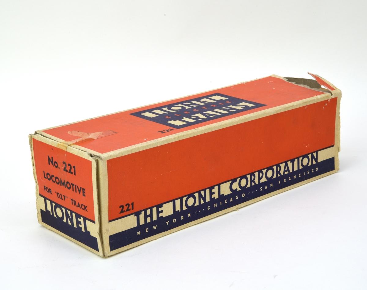 """Eldriven ångloksmodell (:1) från The Lionel Corporation, modellnummer 221, pressgjuten i metall och målat i en mörkgrå nyans. Loket är en detaljtrogen modell av NYC:s Hudsonlok i det strömlinjeformade utförande som formgavs av Henry Dreyfuss 1938.  Formen är rundad och ger ett mer integrerat och aerodynamiskt intryck än mer konventionella lok. Fronten är klotrund med en horisontell fena i mitten och en centralt placerad lykta. Lyktan är fungerande med en liten glödlampa bakom. Även banröjaren är rundad och helt täckt sånär som på tre små slitsar på sidorna. Längs sidorna av loket finns gångplattformar som nås från trappor i fronten med ledstång i blank metall. Loket har ingen uppbyggd skorsten utan bara en öppning med blank ring. Förarhytten är av samma höjd som ångpannan och öppen bakåt. Inne i hytten syns stiliserade mätartavlor och fyrboxluckorna. På hyttens utsidor finns """"221"""" tryckt i silver. Loket har tre par drivhjul och svängbara löphjul. Kolvstång, vevstake och koppelstång är av blank metall.  Till loket hör en förvaringsask i kartong (:2) med tillverkarnamn och modellnummer tryckt i blått mot orange botten. Inuti kartongen finns wellpapp som extra transportskydd."""