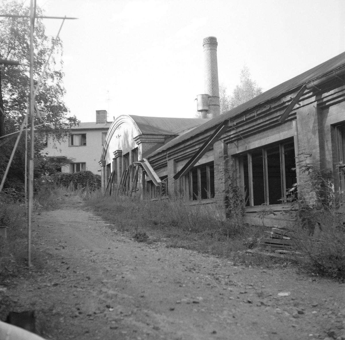 Hjulsbro ABs fabrik inför rivning. Här dokumenterad av Östergötlands museum 1977. Verksamheten på platsen startade 1907 genom grundandet av Hjulsbro Tråddrageri- och Spikfabrik. Från 1923 ägdes fabriken av den kände bankdirektören Jonn O. Nilsson i Linköping och med honom kom verksamheten åter på fötter efter en svår period under  krigsåren och följande depression. Fabriksbyggnaden på bilden uppfördes på platsen för en äldre som blivit lågornas rov 1930. Från 1964 ägdes företaget av Halmstad Järnverk, i folkmun Hamstadstål. I bakgrunden skymtar fabrikskontoret med arbetarebostäder.