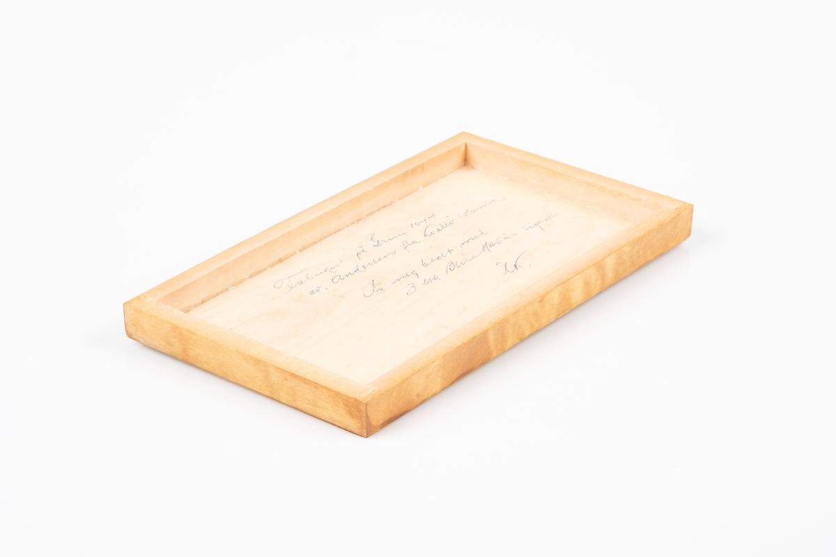 Et rektangulært skrin i tre. Består av bunn og lokk. Det er påført tekst på innsiden av lokket.