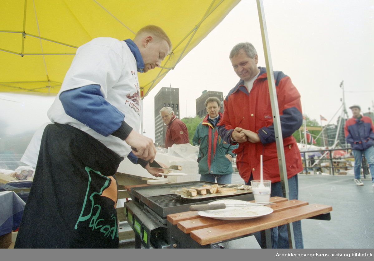 Oslo: Havna. Diverse stemningsbilder. Fiskehandel. Harald Kristoffersen blir servert nygrillet fersk laks av kokken Anders Skjeldal. 17. mai 1996