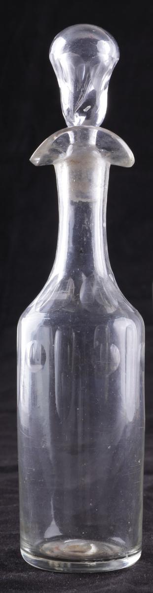 Flasken er slank med dobbel helletut og glasspropp. Den er dekorert med fassettsliping og olivensliping i annethvert felt øverst på kroppen.