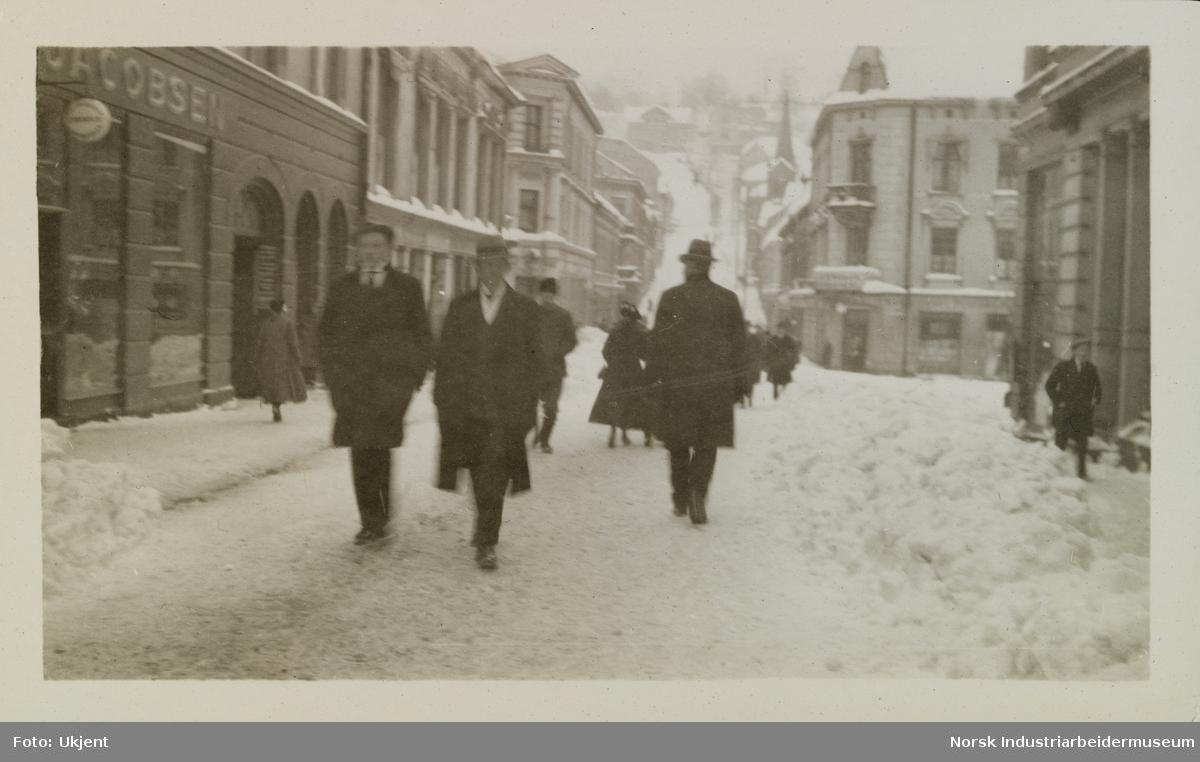 Mennesker går langs snødekt sentrumsgate