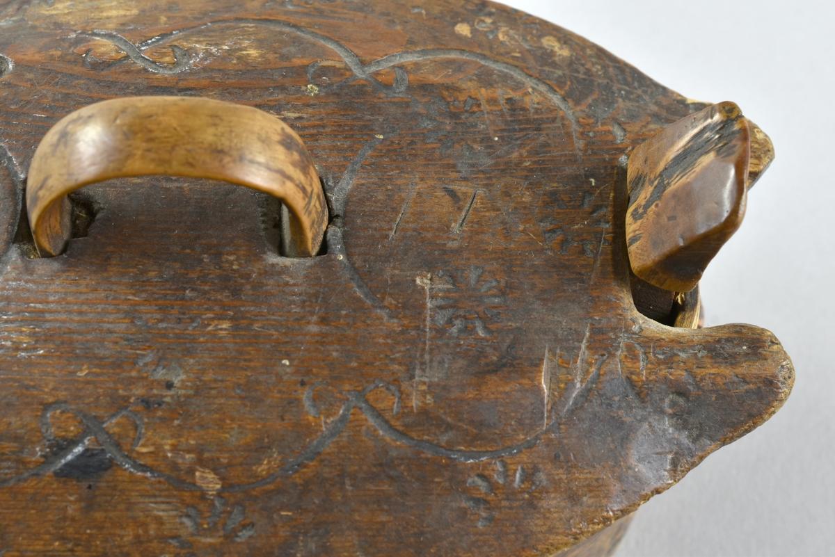 Oval äska i svepteknik. Äskan är dekorerad med inkarvat mönster i form av blommor och girlanger. Askens insida har ett inristat rutmönster. Svepet fäst i botten med träplugg och senare delvis ersatta med små nubb i järn.