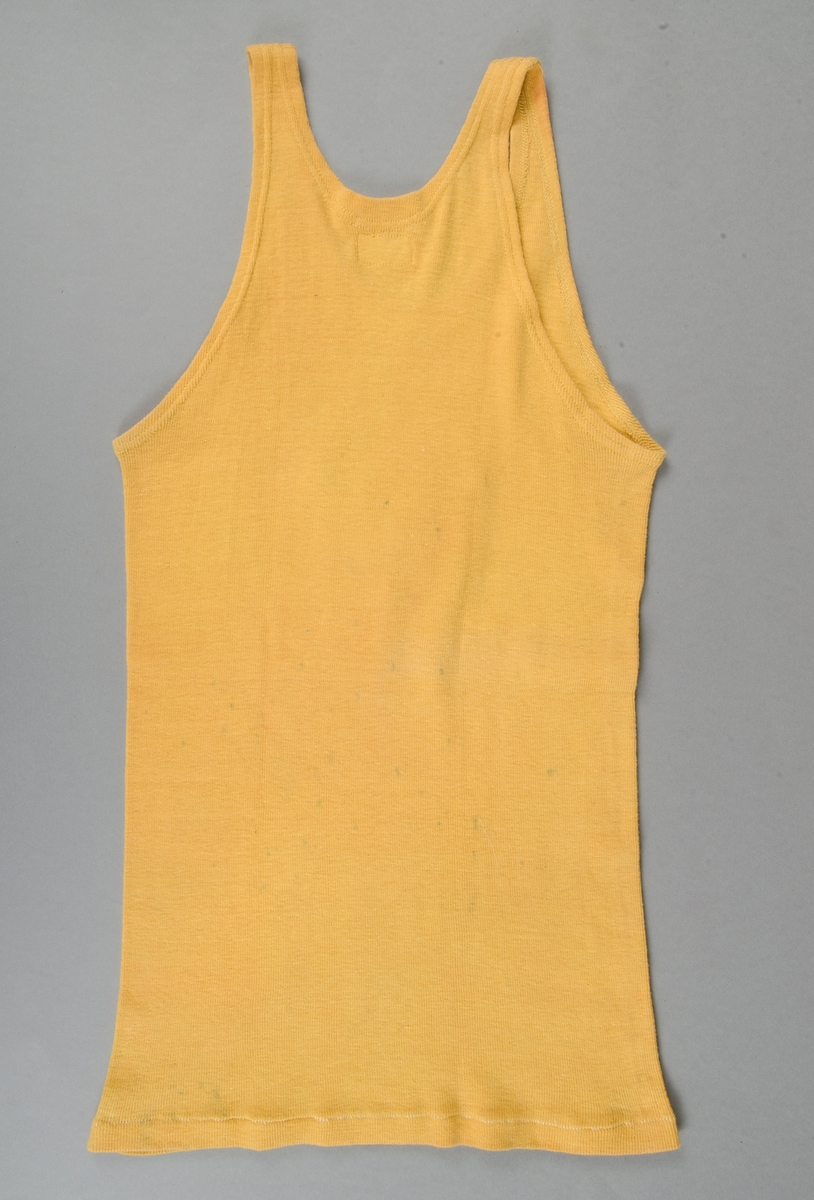 Ärmlös tröja, modell linne, i gul bomull. Mitt fram ett sköldformat märke i rött och vitt ylle med ett svart N. Tröjan är fläckig på ryggen.
