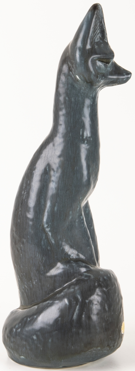 Figurin av formpressad flintgods. Grågrön glasyr. Sittande räv med svansen lindad runt nedre delen av kroppen.