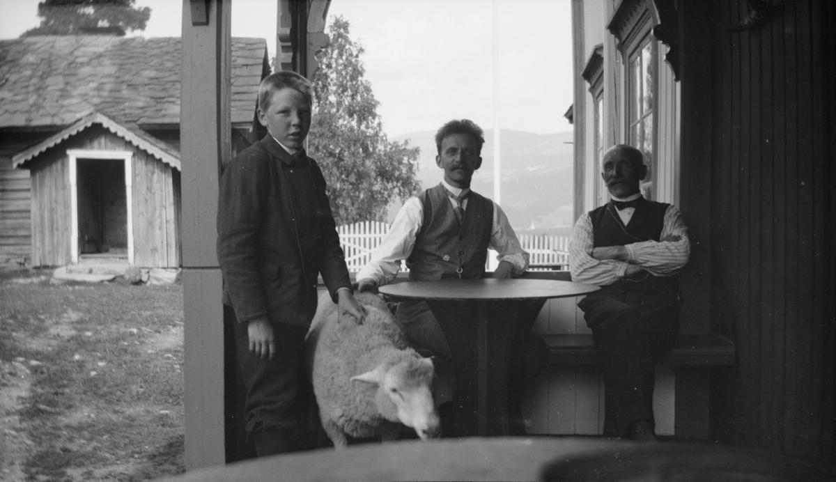 To mann, en gutt og en sau ved bord på verandaen, antakelig på Linjordet i Østre Gausdal