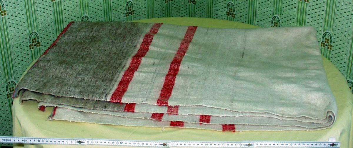 Vevd sengeteppe i ull. Hovedfarger hvit og brun med røde tverrstriper.