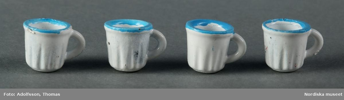 Vit kaffeservis med turkos dekor i form av prickar: a) kaffekanna, b) gräddkanna, c:1-2) sockerskål med lock, d-g) fyra koppar och h-k) fyra fat. Tillverkade av metall. Kaffeservisen ska stå på matbordet (NM.0333310 a) mitt i matsalen i dockskåpet NM.0331721+.