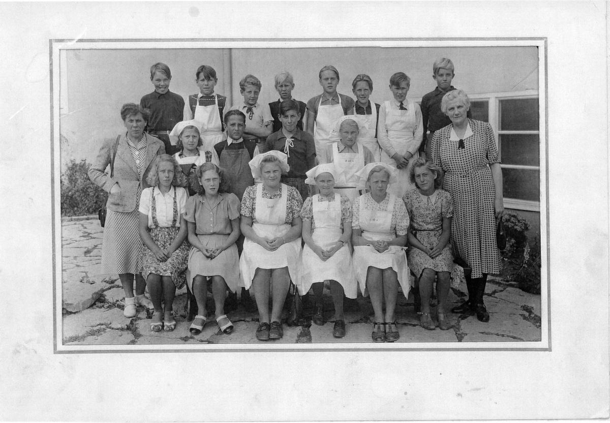 Gruppfotografi av en skolklass som möjligen är klädda för hemkunskapslektion. De flesta elever är iklädda förkläde. Två lärarinnor är med på bilden.