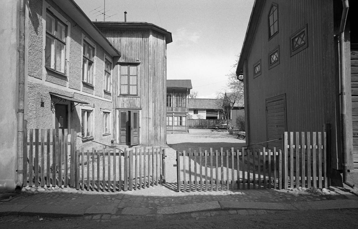 Exteriör av boningshus, trä, i två våningar. Trappan finns förmodligen i den rundade delen. Till höger ligger en förrådsbyggnad i två våningar, med spröjsade fönster. Äldre kvarter. Fotografens anteckning: Dokumentation av fastigheter i kvarteren söder och norr om ån. Bilder och beskrivning finns på Arboga Museum.